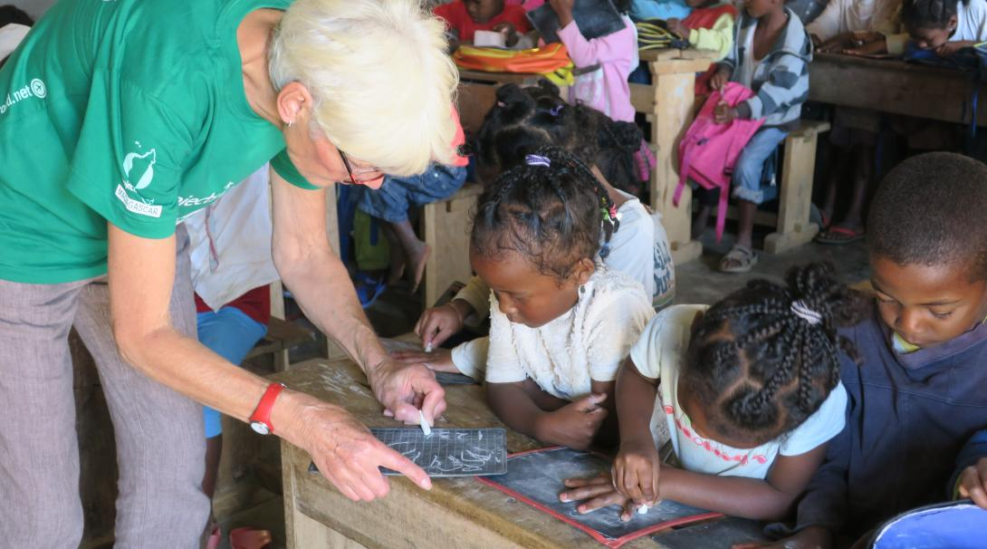 On a volunteer abroad program for older adults, a woman works with school children in Madagascar.